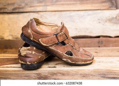 Men's leather sandal isolated on wooden background , Worn out
