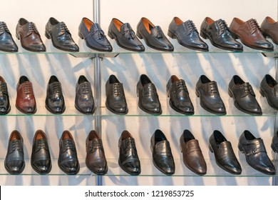 Men's leather shoes on the shelf in the store. Racks in the store of clothes and accessories. Shelves with stylish men's shoes. Many classic shoes and boots