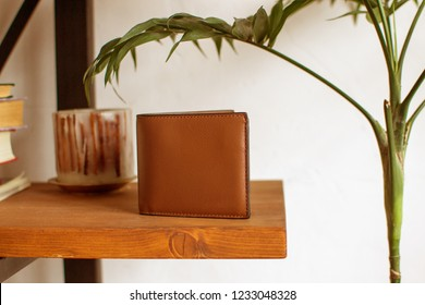 mens leather wallet on a wooden shelf, leather wallet (horizontally, toned)