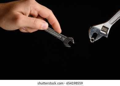 Men's left hand holds the open-end wrench, in front of her Allen wrench while holding the nut