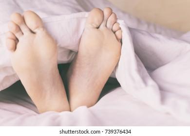 Men's legs, and alarm clock
