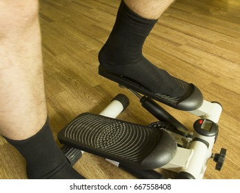 Men's legs in black socks stand on a stepper (side view)