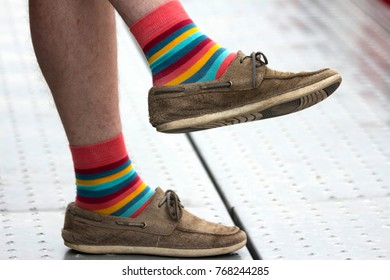 Men's legs in brown loafers and striped colorful socks close-up