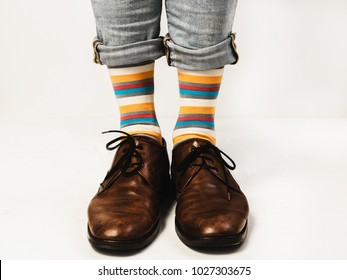 Men's legs in jeans, bright socks and stylish shoes