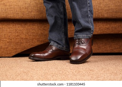 Men's legs in jeans shod in classic brown Oxford shoes