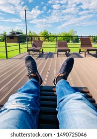 Mens legs in jeans and sneakers lie on deck chair against the blue sky.