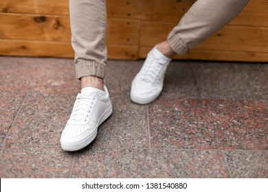 Men's legs in leather fashion white sneakers in stylish beige pants. Trendy casual outfit. Details of everyday look. Street fashion. Close-up.