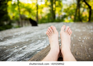 Men's legs lying on the ground with the nature landscape