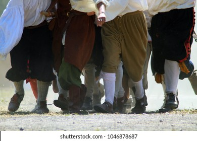 A lot of men's legs in medieval clothes (costumes). Men running in the sand field. Living history festival. French revolution. The riot. Battle. Attack.