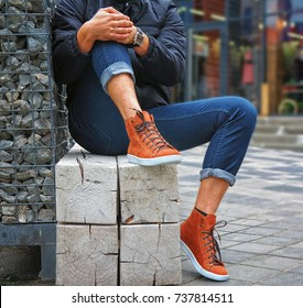 Men's legs in orange sneakers and jeans on the street