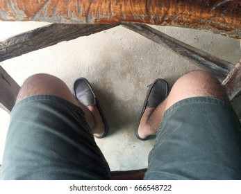the men's legs in a relaxed posture.at the room