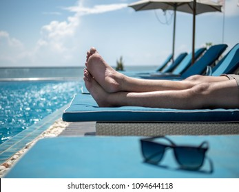 Men's legs resting in a swimming pool. Summer holiday traveling concept design banner with copyspace.