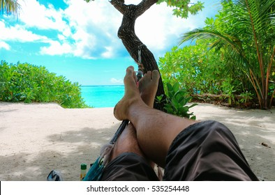 Men's legs in shorts lying in a hammock on the sand beautiful tropical beach in the shade of palm trees. Maldives.