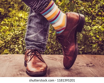 Men's legs in stylish shoes, bright, multi colored, variegated socks with Christmas and New Year's patterns on the wooden terrace on the background of green trees. Beauty, fashion, elegance