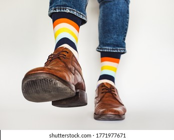 Men's legs, trendy shoes, blue jeans and variegated, long socks on a white, isolated background. Close-up. Concept of style and elegance