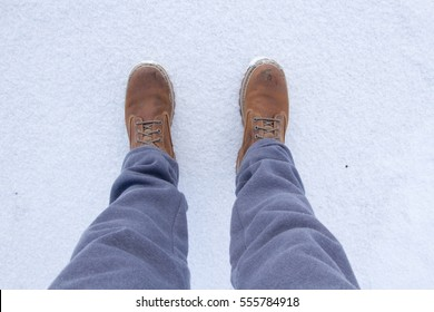 Men's legs in work shoes and gray sweatpants, snow on background, first person perspective