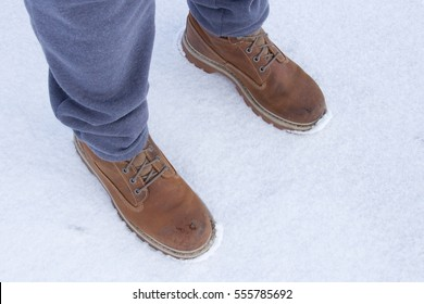 Men's legs in work shoes and gray sweatpants, snow background, side perspective