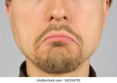 men's lips corners down, expressing sadness, closeup