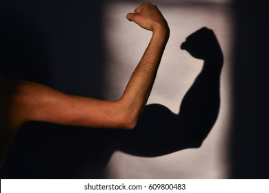Men's muscles, reality and expectation. Sports and training in the gym. Man's hand and a shadow on the wall. Expectation vs reality