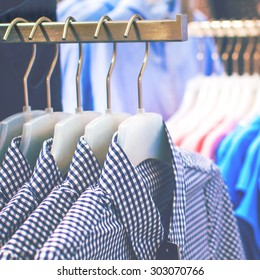 Men's plaid shirts on hangers in a retail shop