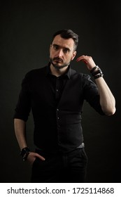 men's portrait in a black shirt and black vest with a watch and leather accessories on his hands