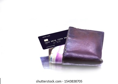 men's purse with money, credit and debit cards on the white tables