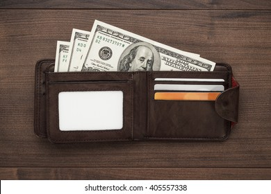men's purse with money, credit and debit cards on the wooden table