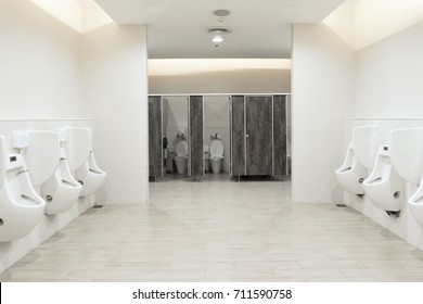 Men's room urinals discharge ,Toilet bowl in a modern bathroom with bins and toilet paper,flush toilet clean bathroom