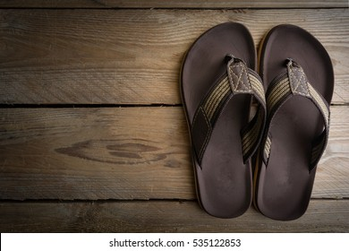 Men's sandals on wood floor.