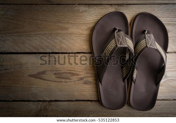 Men's sandals on wood floor.