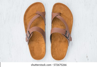 Men's sandals top view on rustic wood background.