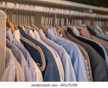 Men's shirts in different colors on hangers in wardrobe.