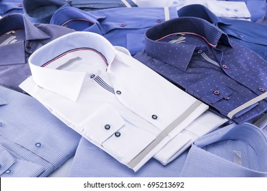 Men's shirts folded new: white, blue and bright blue on a blue background.