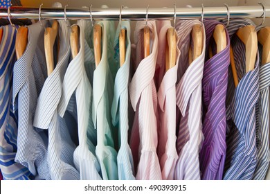 Men's shirts are hanging in the closet. Men's Clothing lying in the locker room. The order in the men's wardrobe.