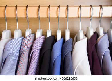 men's shirts on hangers in wardrobe