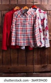 Men's shirts on a wooden fence in a fitting room.