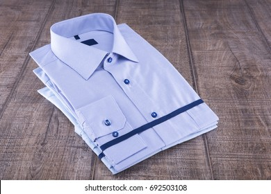 Men's shirts on a wooden table. Folded. The background is gray.