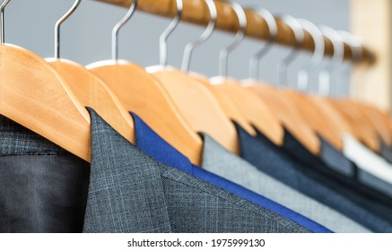 Mens shirts, suit hanging on rack. Hangers with jackets on them in boutique. Suits for men hanging on the rack. Mens suits in different colors hanging on hanger in a retail clothes store, close-up.