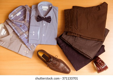 Men's shirts, trousers, bow tie, belt and shoes lying on wooden background