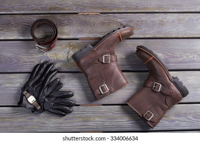 Men's shoes and accessories on a wooden background.