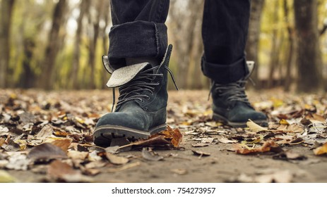 Men's shoes in autumn leaves. A man walking in a park full of autumn leaves