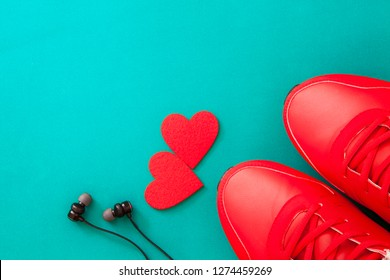 men's shoes, heart and black headphones top view,red sneakers headphones and two red hearts on a blue background
