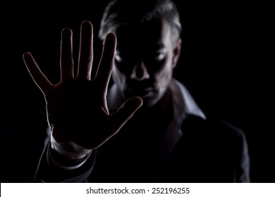 Men's silhouette in the dark shows the stop hand