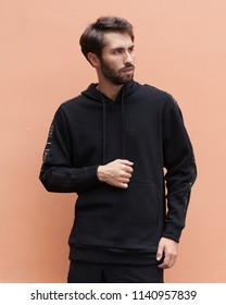 Men's street youth modern fashion. A young male hipster with a beard in a black sweatshirt and black shorts, on a brown wall background