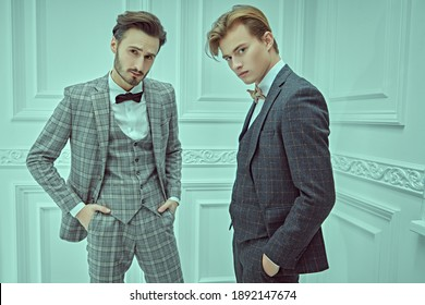 Men's style. Portrait of two elegant young men in classic three-piece suits standing in white luxury apartment.