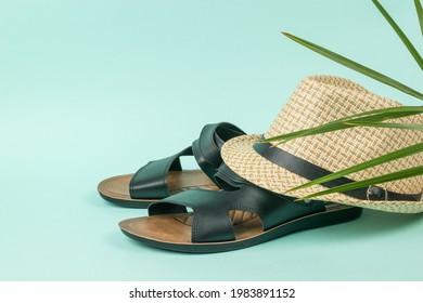 Men's summer hat on black sandals on a blue background. Summer men's shoes.