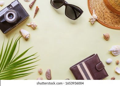 Men's traveler accessories: green tropical palm leaf, photo camera, seashells and sunglasses are on yellow background with copy-space. Top view travel or vacation concept, flat lay summer background