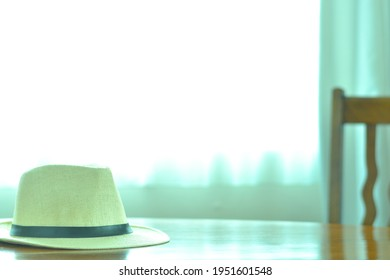 Men's trilby hat.  put on a reflect brightly walnut oval dining table. window is bright.   This expensive antique furniture is made in England.  clear background with soft focus image.