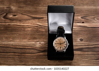 men's watch in a box on a wooden background
