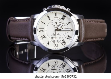 Men's watch with brown leather band on black background.
